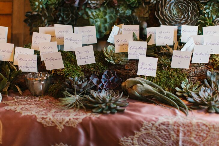 "Having seen one of Flowers by Semia's living art pieces, Rachel knew she and John had to have one for their reception. Semia created a large, eye-catching display of succulents, air plants and moss in rich shades of green, slate blue and purple, which created the backdrop for the moss-covered log that held all of the handwritten escort cards. ""Those succulents are still happily living at our home,"" Rachel says."
