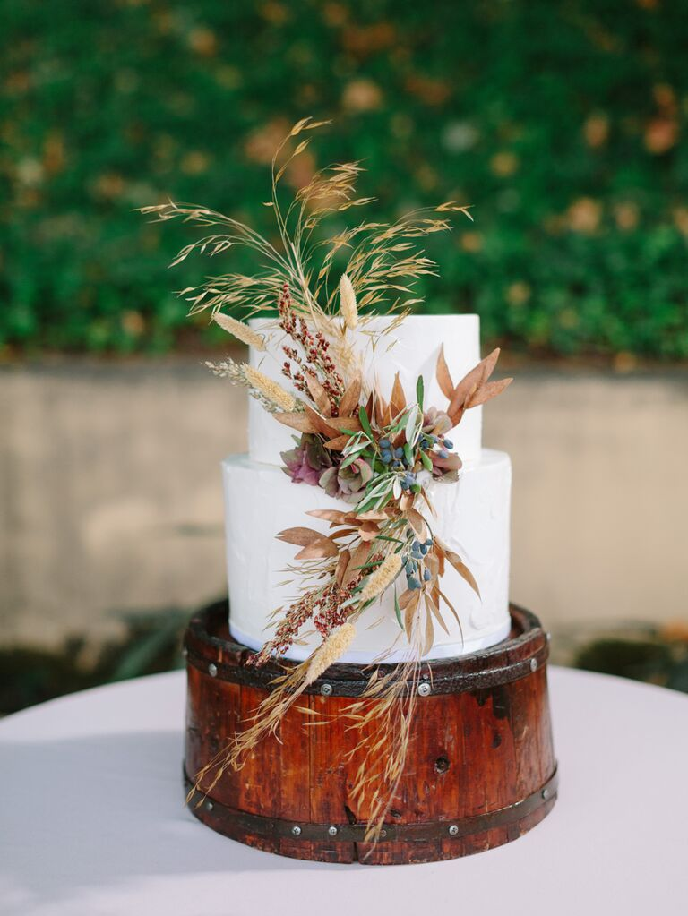 Simple two-tier wedding cake with fall floral cluster
