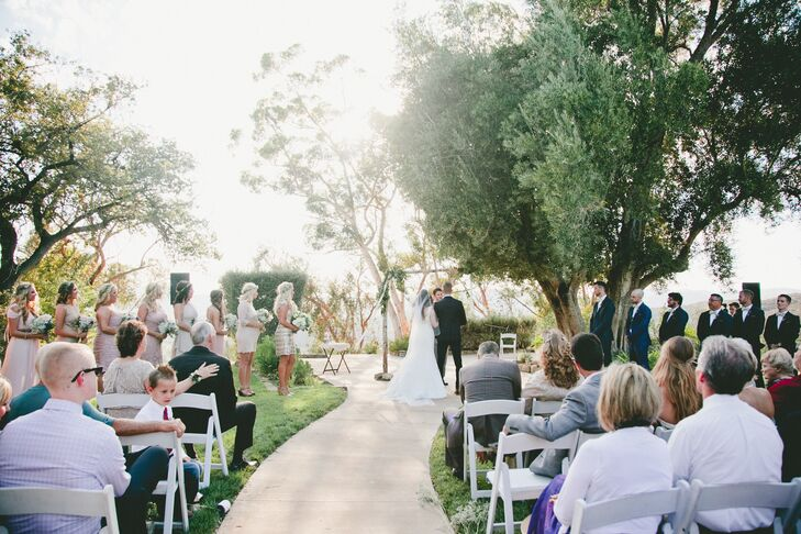 The ceremony location featured beautiful views of Malibu Canyon. A birch arch with greenery and sheer fabric awaited the couple at the end of the aisle.
