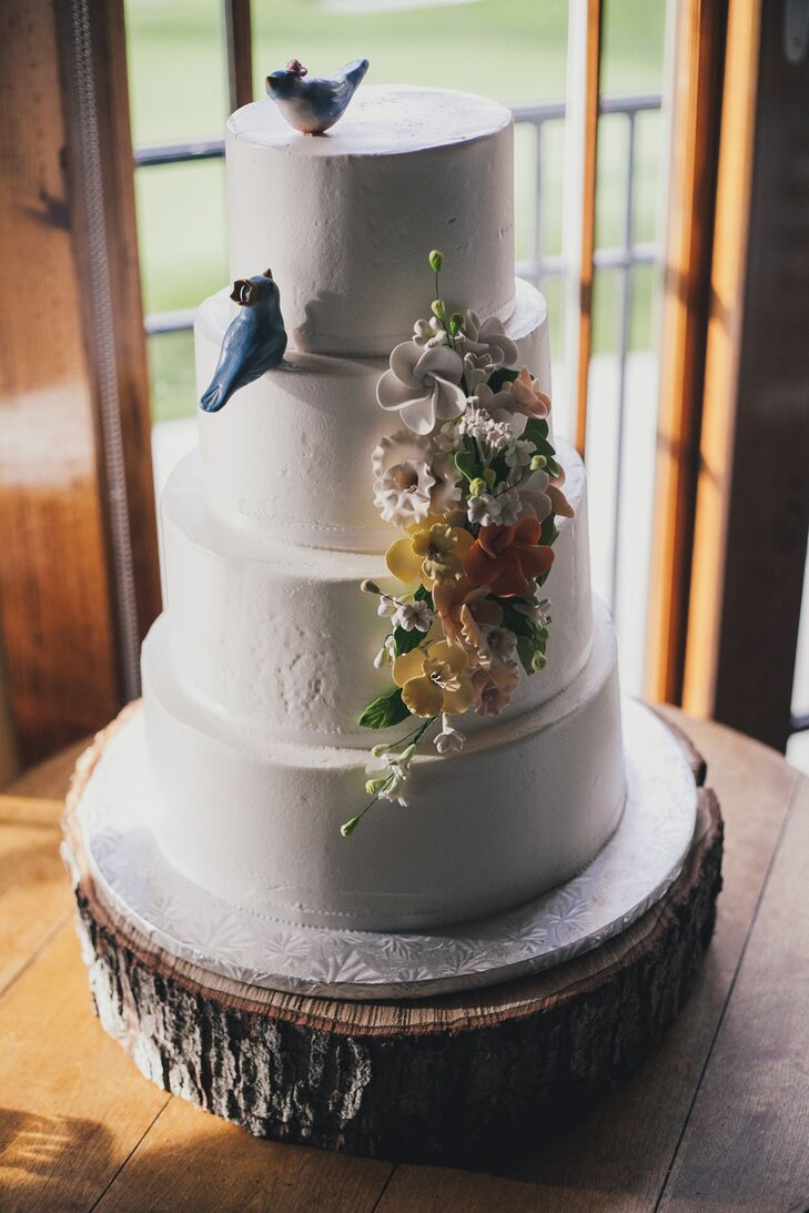 Four-Tiered White Wedding Cake with Floral and Blue Bird Accents