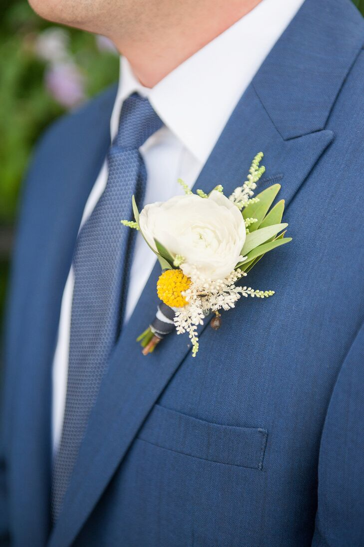 Sean's boutonniere brought out their nautical theme with a natural touch. Wrapped in white-and-navy-striped ribbon, a white ranunculus, eucalyptus leaves, white astilbe and yellow craspedia arrangement from Twisted Willow Flowers topped his notched lapel.