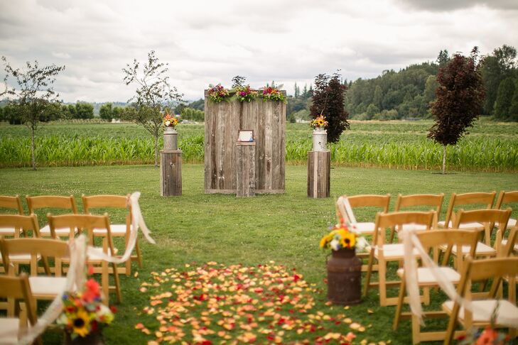 The couple was married at an altar surrounded by wood pillars and rustic wood panel backdrop at Craven Farm in Snohomish, Washington. The aisle was decorated with wildflower arrangements, drapery and colorful petals.