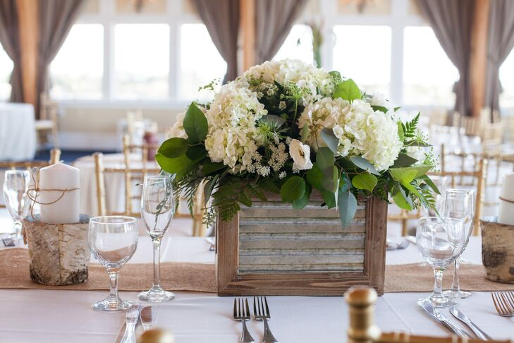 Flower Cart Florist set each family-style table with a rustic touch. Exposed-wood breakaway vases were filled with white hydrangeas, baby's breath, greenery, white rosebuds and white lisianthus. Burlap runners lined the tables.