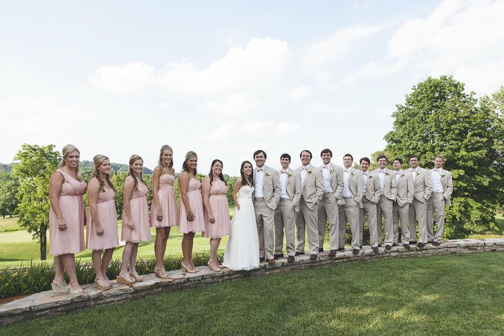 The bridesmaids chose a dress in the same pink color and fabric from J. Crew's Wedding Collection. I loved the look of all the different dresses together on the big day, says Carter. The groomsmen kept it casual in khaki suits and matching pink ties.