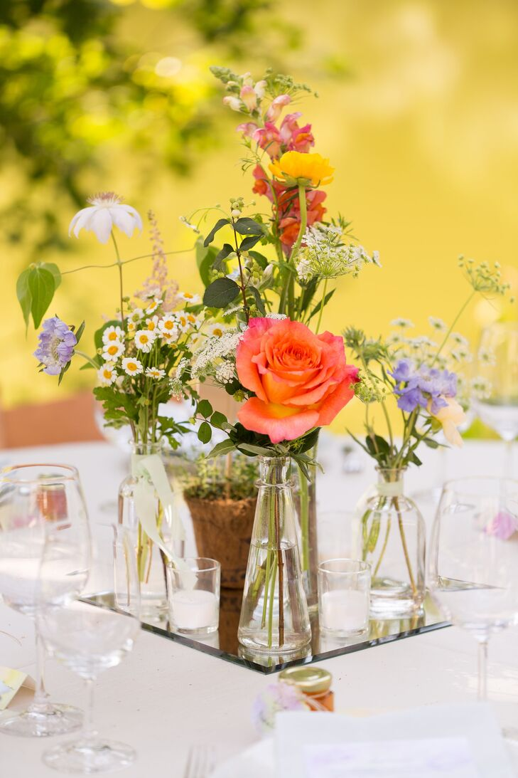 Small arrangements of wildflowers were displayed in glass bottles, giving the centerpiece decor a unique, natural touch.