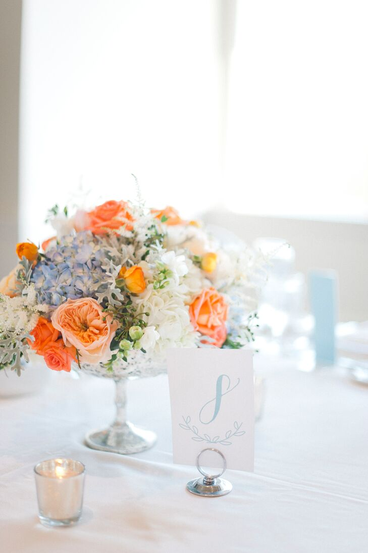 Festivities created lush bunches of coral, blue and ivory blooms like garden roses, hydrangeas, astilbes and tea roses for the centerpieces. Arranged in mercury glass bowl vases, the flowers added a cheerful pop of colors to the tables and were low enough for guests to see one another and converse with ease.