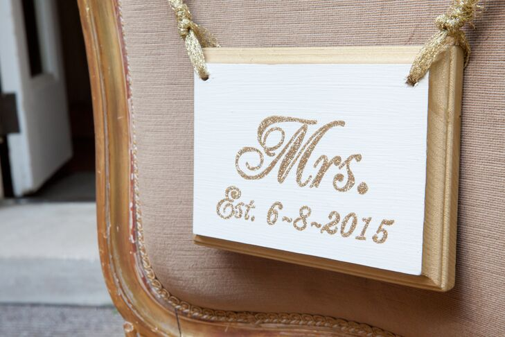 """Sicilia and Samuel sat at their sweetheart table labeled with """"Mr."""" and """"Mrs."""" chair signs, displaying their wedding date in gold elegant font with a white wood backdrop."""