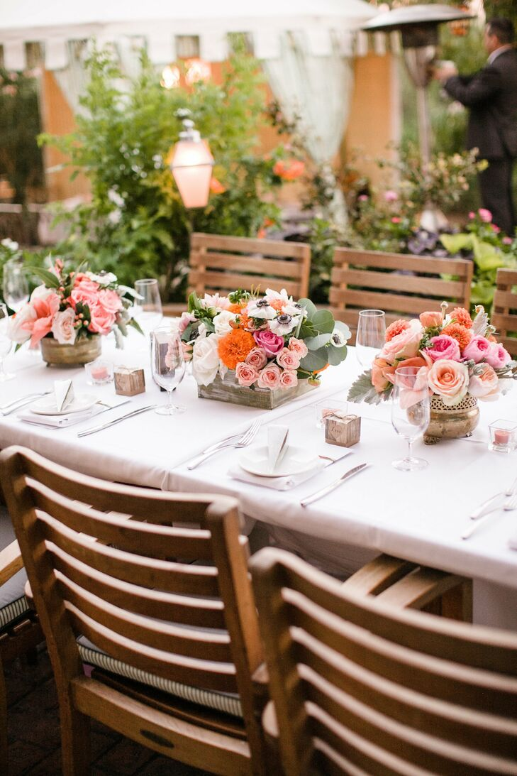 Tables at the reception were styled in drastically different ways. This one favored wooden chairs and pink and orange floral arrangements full of peonies and roses.