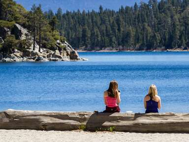 two women sitting on the shore of lake tahoe