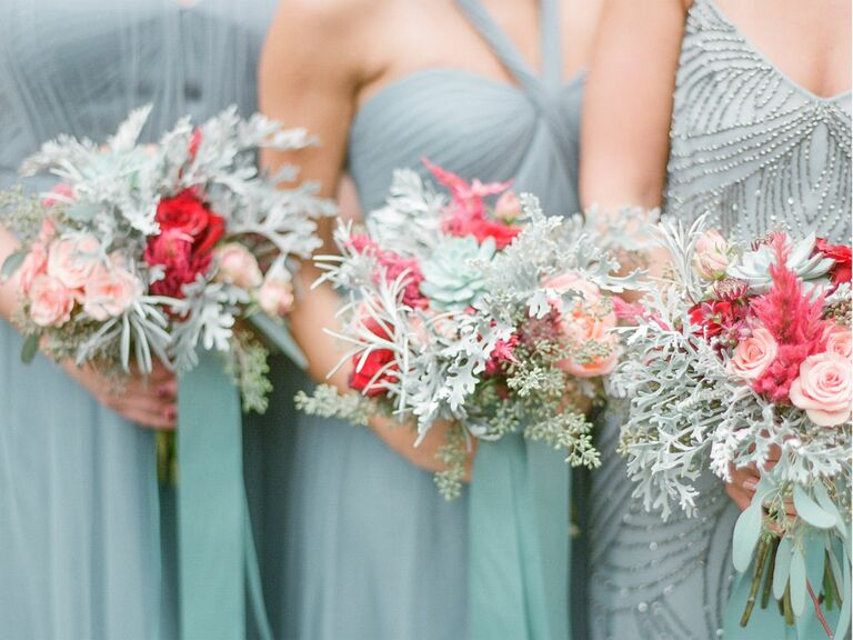bridesmaids in blue gray holding wild bouquets