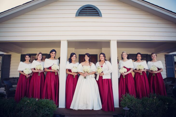 """""""I wanted the bridal party to look elegant and timeless,"""" Courtney says. She chose long, satin red gowns from Alfred Angelo, which she paired with white fur wraps."""