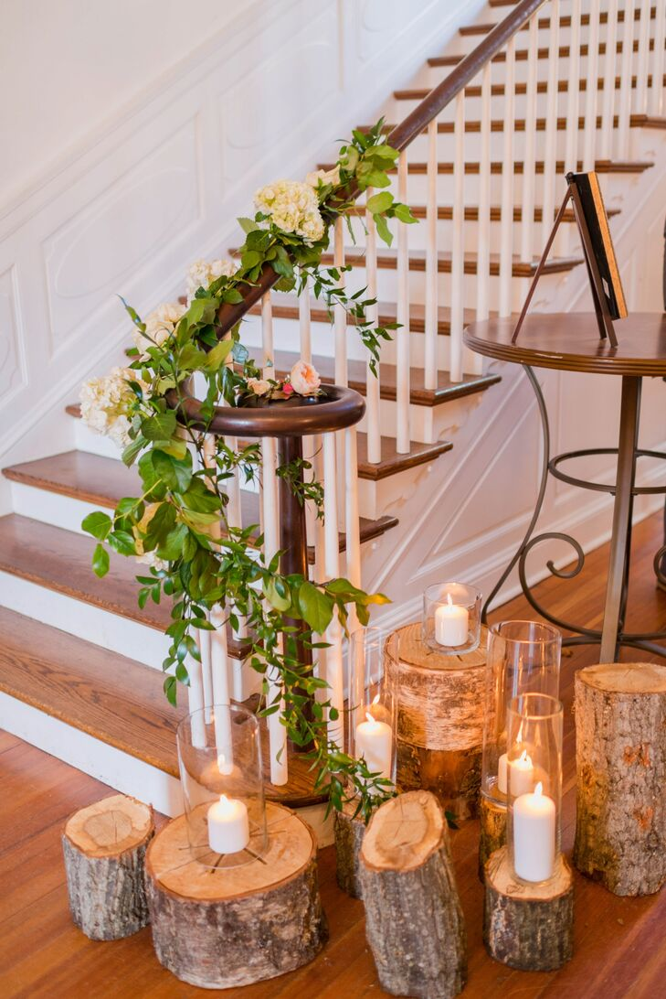 Rows of wooden logs with candles on top stood next to the staircase near the entrance of Rust Manor House in Leesburg, Virginia, adding a rustic touch to the wedding decor.