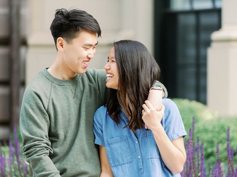 Couple holding hands and laughing during engagement session