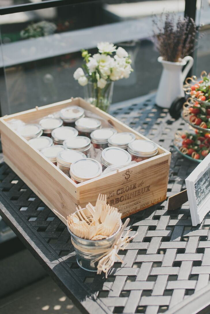 A wooden box held an assortment of lavender-sugar fruit salads stored in mason jars for guests to eat and enjoy during the cocktail hour.