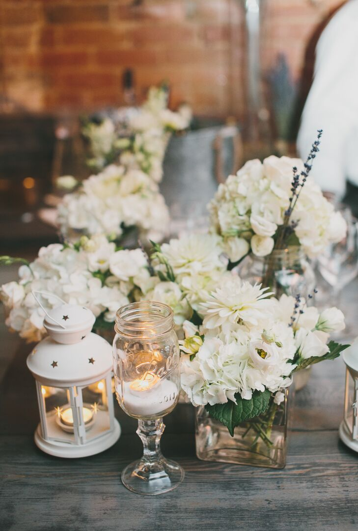 Small arrangements of white hydrangeas were paired with candles in mason jars and white lanterns, giving the centerpiece decor a modern, romantic look.