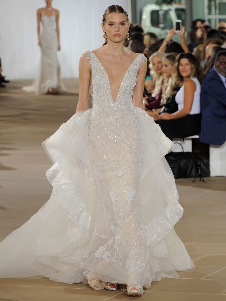 Ines Di Santo Fall 2019 glamorous embellished wedding dress with voluminous side ruffles and a plunging neckline