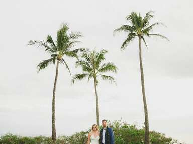 bride and groom in front of palm trees