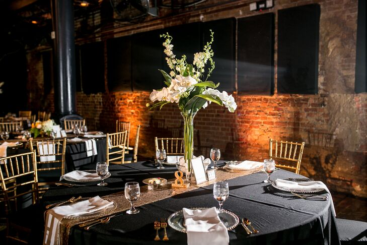 Black linens with gold sequin runners draped down dining tables, in addition to tall centerpieces filled with white blooms that decorated the middle of the displays.