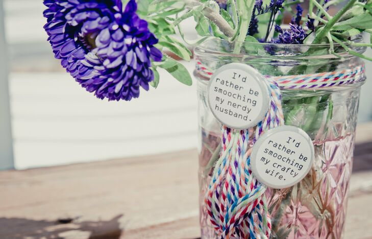 The backyard was decorated with bright purple gerbera flowers that were placed in glass jars with multicolored strings and held together by two pins that featured romantic and witty sayings.