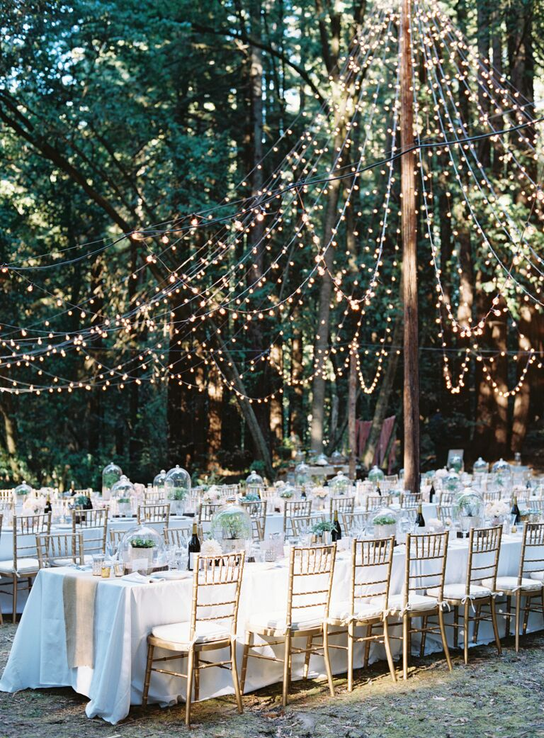Rustic outdoor string lights over reception tables