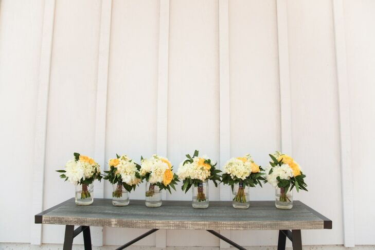 Ashleigh and her bridesmaids carried bouquets of yellow and white flowers with leafy accents down the aisle at the ceremony.