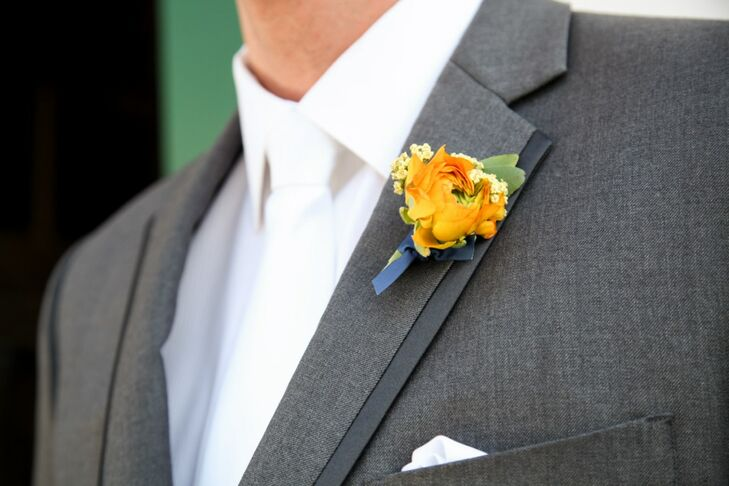 The groom and groomsmen wore marigold-colored ranunculus boutonnieres fastened to their lapels and suspenders on the wedding day.