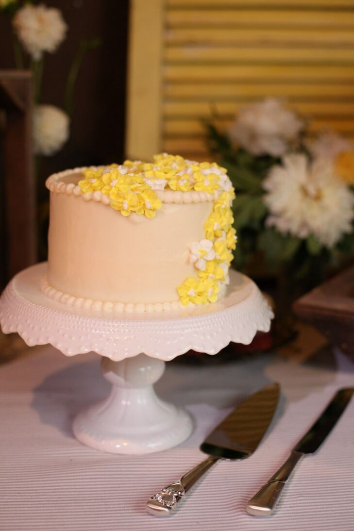 The couple's wedding cake was a yellow and white confection that was a single tier decorated with yellow hydrangea sugar flowers.