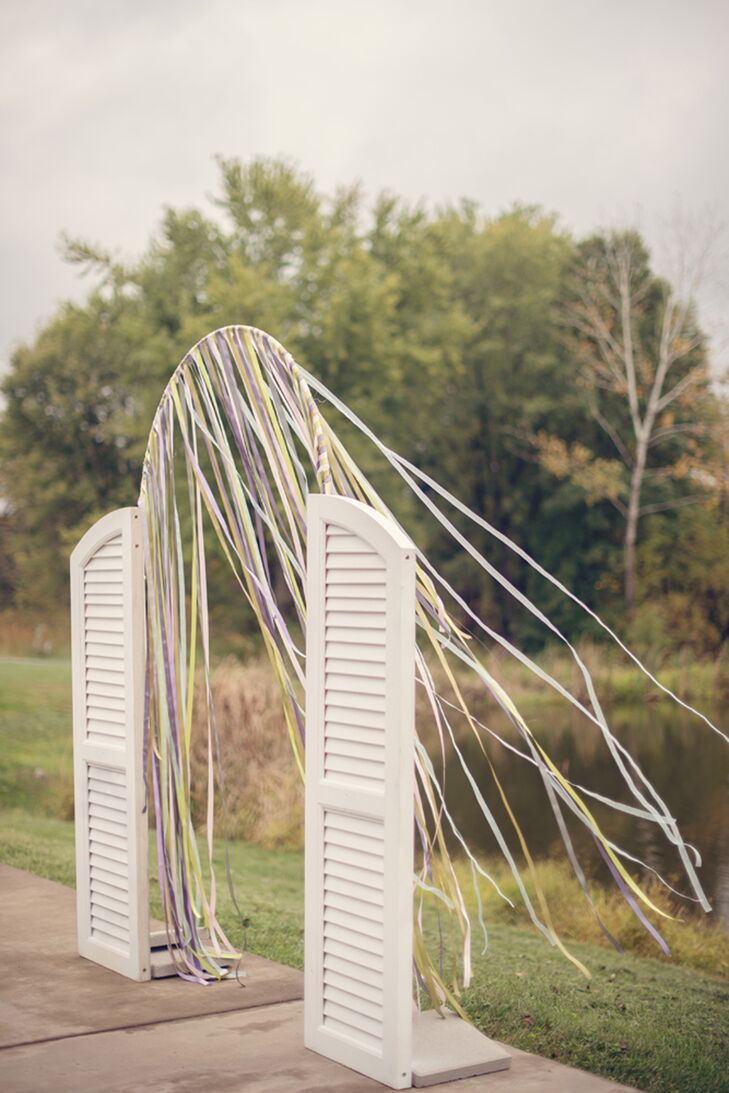 Now this is a new way to use window shutters! Erin and Cory's wedding arch was accented with twin white shutters. Colorful streamers decorated its  thin, wire frame.