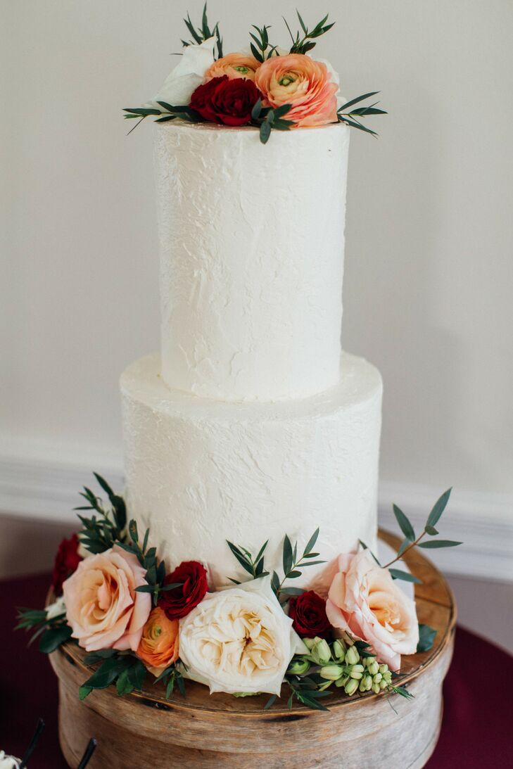 Tall-Tiered, All-White Cake Accented with Romantic Roses and Ranunculus on Rustic Stand
