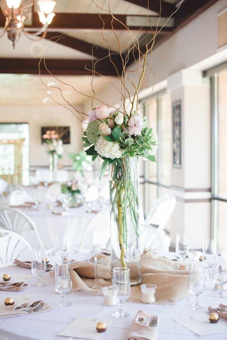 The florists at Dayspring Designs infused the clubhouse at the Lakeridge Country Club with the beauty of the summer season with a mix of high and low centerpieces overflowing with full ivory and blush blooms. The tall arrangements featured fluffy hydrangeas, hyacinth and curly willow displayed in high hurricane vases.