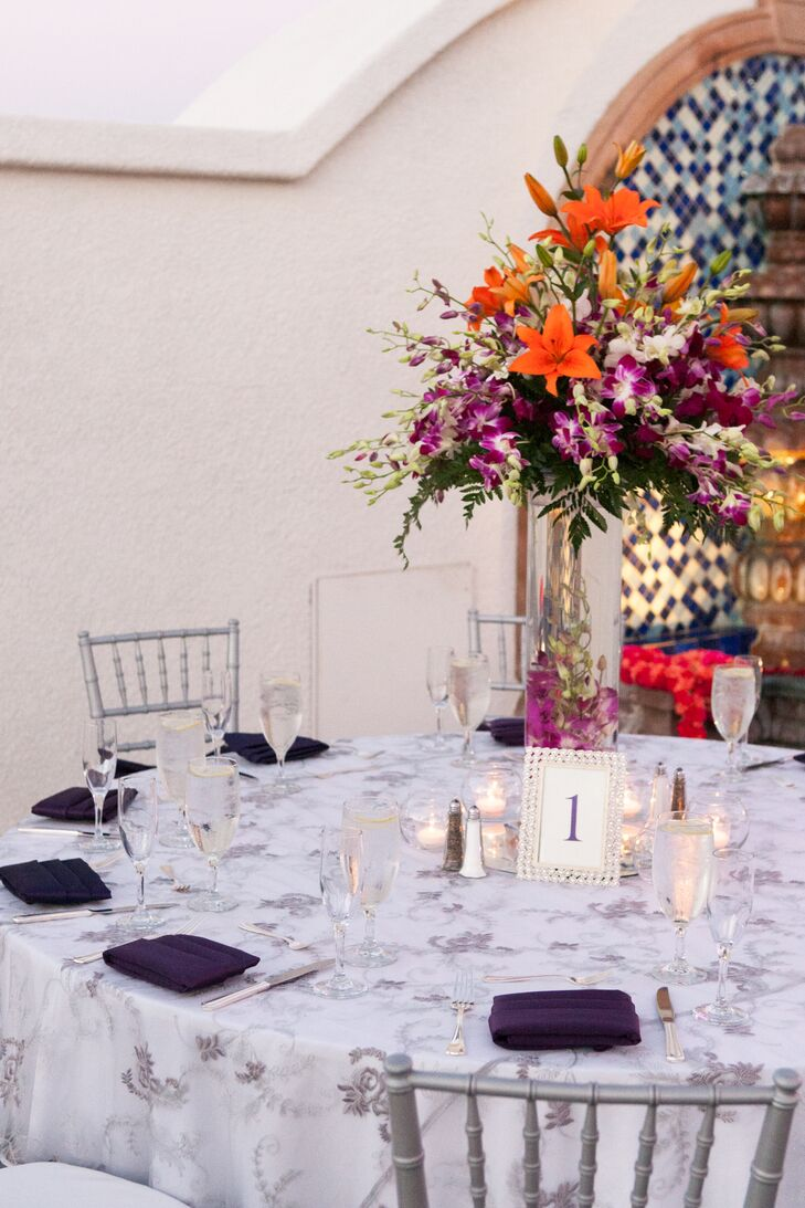 Dining tables were dressed in silver and white tablecloths surrounded by silver chiavari chairs. Tall flower arrangements of orange lilies and purple orchids decorated the table, with simple framed white table numbers.