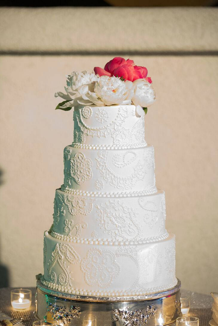 The ivory four-tiered wedding cake decorated with a beaded pattern was topped with ivory and red peonies.