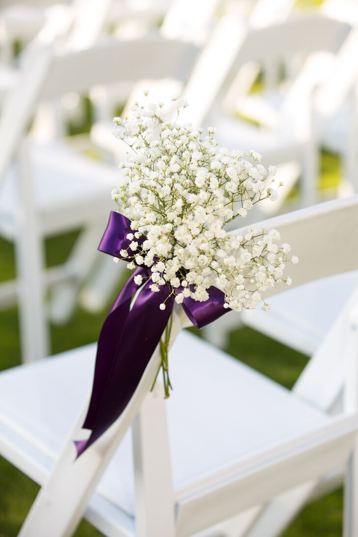 Simple aisle decorations of white baby's breath tied with purple ribbon decorated the ceremony.