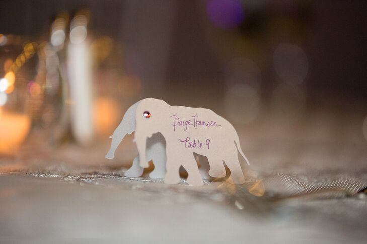 Elephant escort cards with the guest's name and table number were written in purple ink.