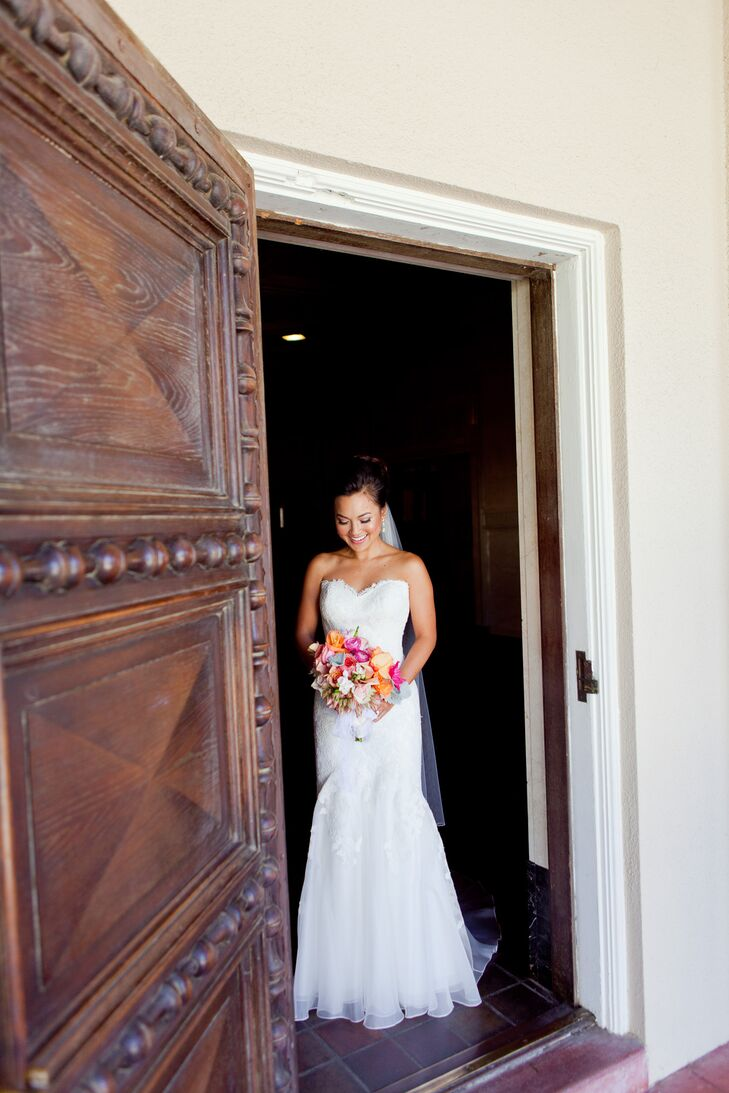 The bride wore an ivory strapless heart shaped dress designed by Jinza Couture Bridal and held her flower bouquet.