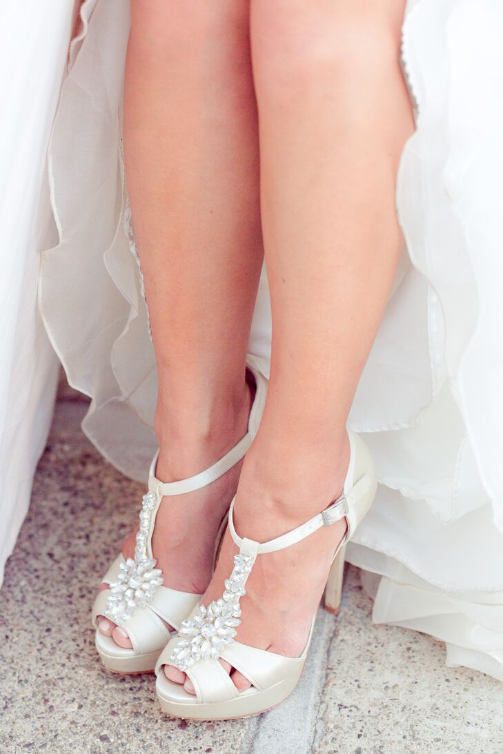 The bride wore ivory heeled shoes with ankle straps, accented on the tops with crystals.