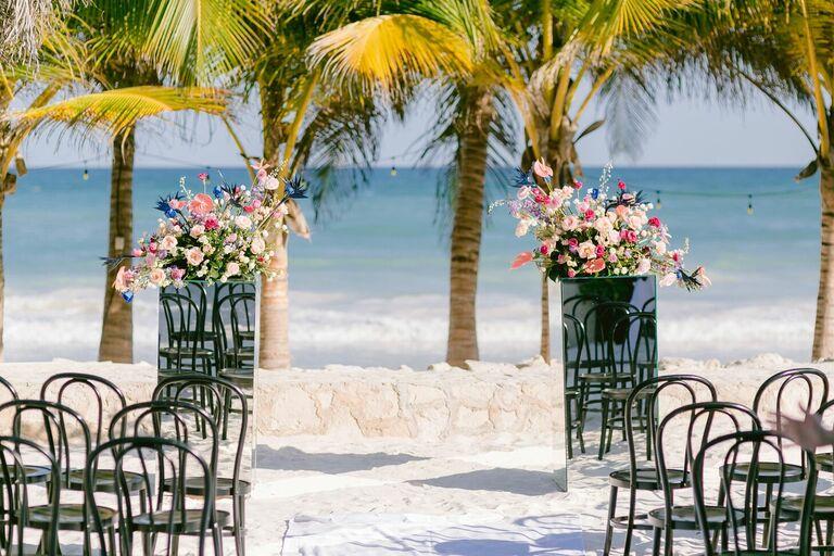 Beach ceremony with mirrored flower pedestals
