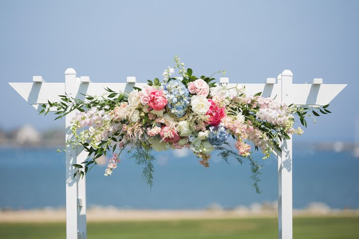 The ceremony took place outdoors on the expansive lawn at Wentworth by the Sea in Rye, New Hampshire. With the sparkling waters of the Atlantic forming the backdrop, Amy and Steven kept the decor on the understated side, opting for a few summery bunches of blue and blush hydrangeas for the aisle and a striking, cascading arrangement of peonies, roses, hydrangeas and stock for the simple wedding arch.