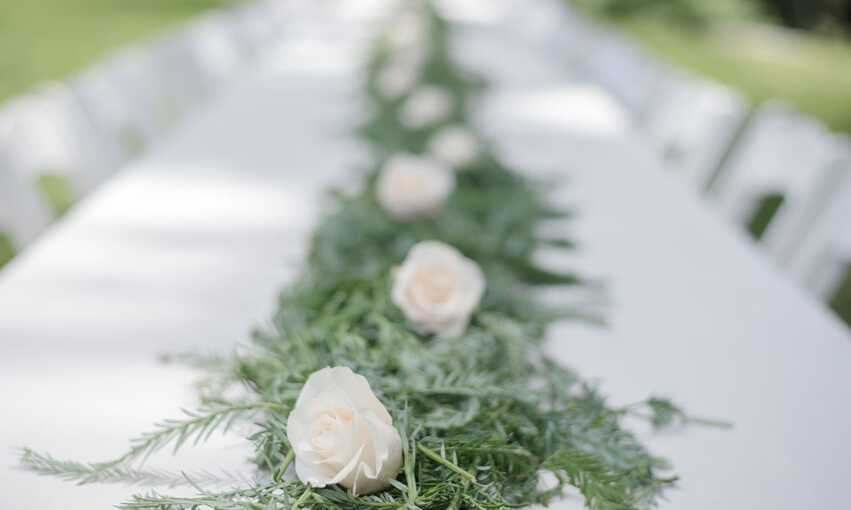 Long white table with green and white floral centerpiece