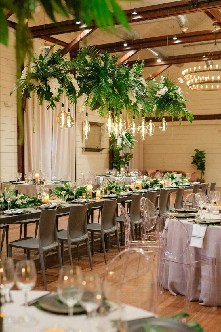 Ballroom wedding reception with tropical hanging greenery and Edison bulbs