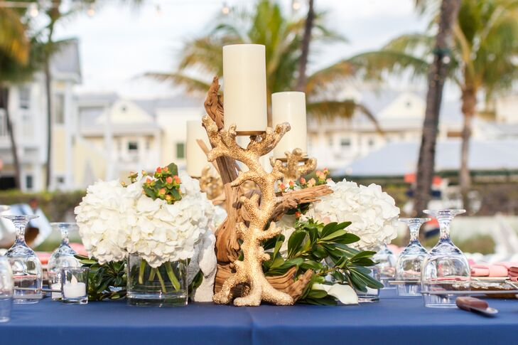 The couple's planner and florist, Soiree Key West, brought the beach into their reception with a few fun twists. Orange hypericum berries popped from bunches of white hydrangeas along the tablescape as  greenery, driftwood and candles atop gold coral-inspired accents filled the center.