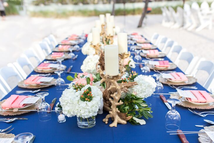 Soiree Key West combined both the couple's beach and preppy wedding styles in their reception.  White hydrangeas, greenery, driftwood, and orange hypericum berries lined the table as gold coral-inspired candlesticks accented the arrangement. Navy linens, bright coral napkins and sea-sponge-inspired chargers were used at each place setting.