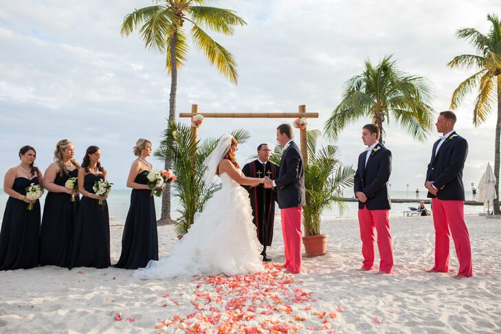 To go with the couple's preppy wedding style, the bridesmaids wore classic floor-length dresses in navy with a string of pearls. The groomsmen wore matching navy Ralph Lauren Polo blazers with fun coral pants from Vineyard Vines for the beach ceremony.