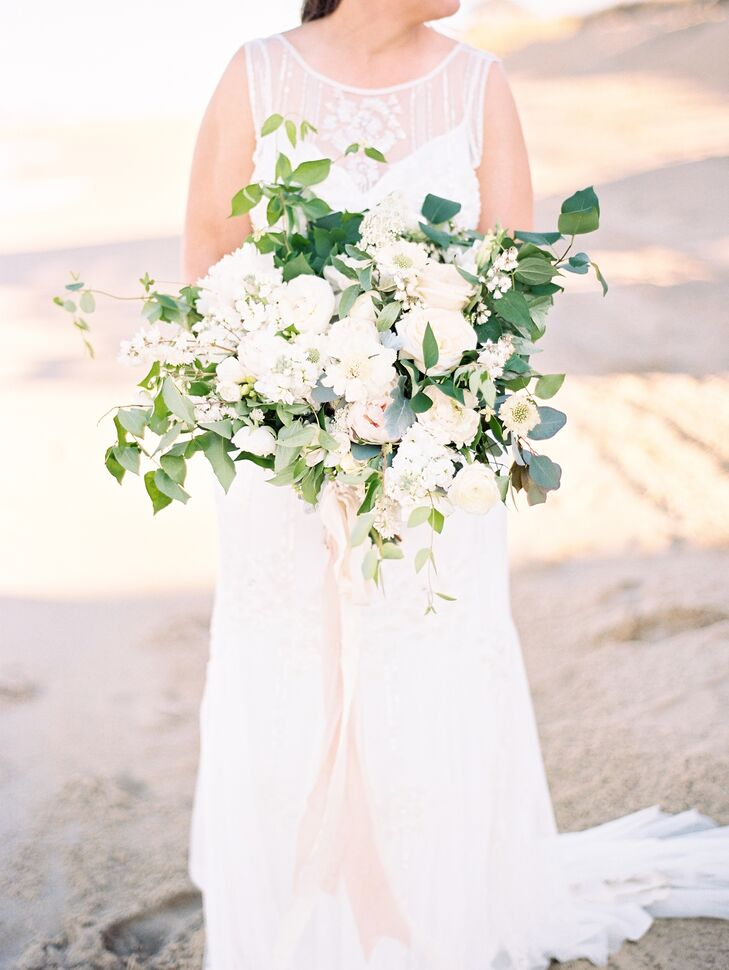 """""""My bouquet was one of the prettiest things I have ever seen,"""" Taylor says of her gorgeous arrangement by Amore Events by Cody. She wanted a natural, soft palette of green and white to go with the sea-inspired palette. Her bouquet was filled with ranunculus, peonies, garden roses, eucalyptus, olive, honeysuckle and scabiosa."""