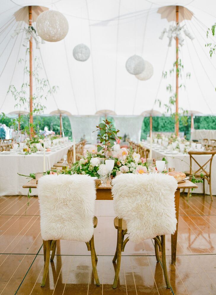 Plush, furry goat pelts covered the couple's chairs at their flower-topped sweetheart table. It overlooked the dance floor and the long feasting tables for their guests.