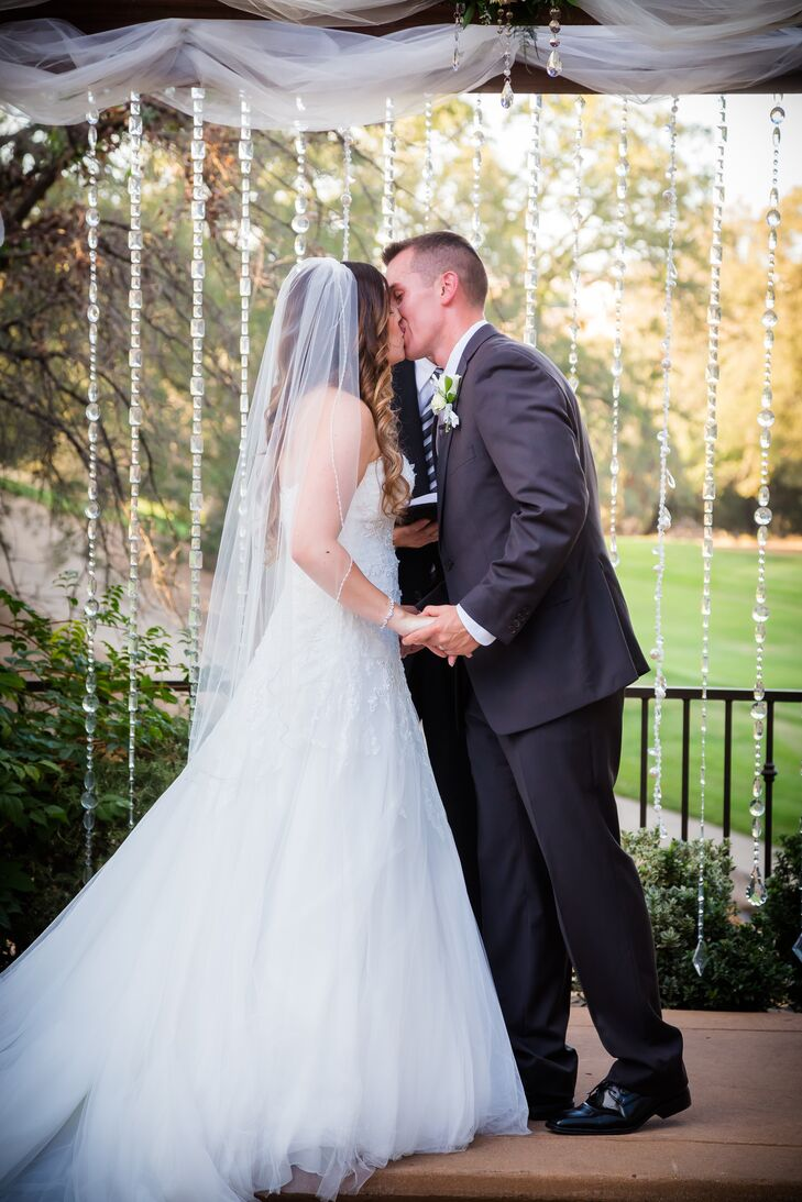 Marisa and Mikhail shared their first kiss at the wedding arch that was draped with strings of crystals and covered with white linens. Marisa wore a traditional ivory veil made of tulle on the day of the wedding, which went nicely with her ivory Pronovias dress.