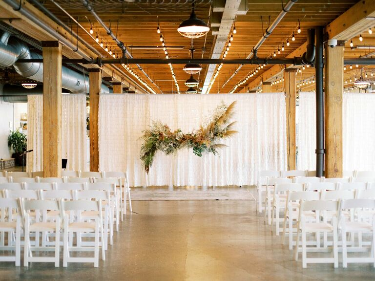 Loft wedding ceremony with folding chairs and hanging pampas grass altar arrangement