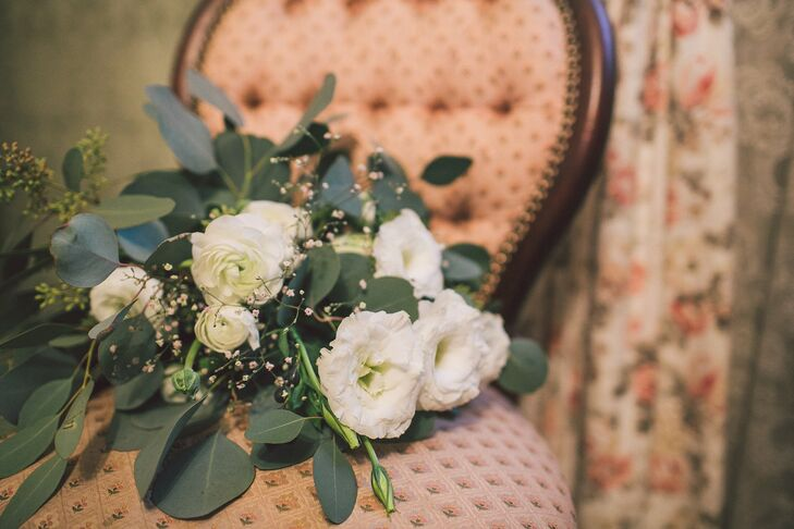"Melanie held a bouquet of greens, such as leaves and eucalyptus, mixed in with scattered ivory flowers. ""I love greenery, so we had eucalyptus as the bulk of our floral arrangements with some white added in,"" Melanie says. ""We wanted it to be warm and inviting."""