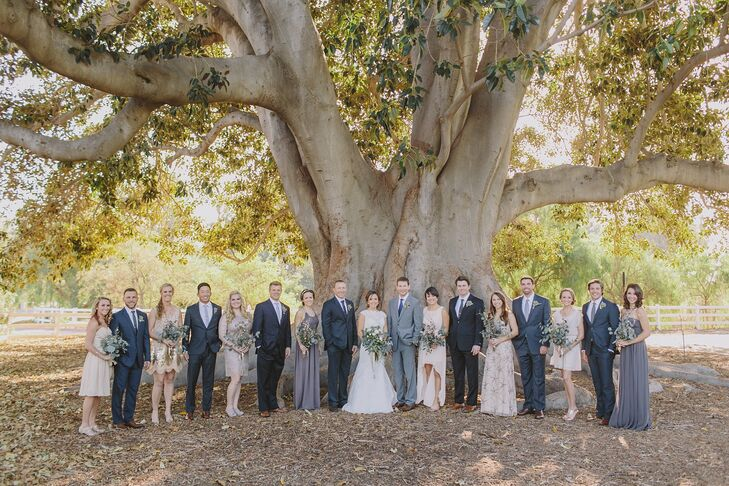 The couple stood in the middle of their wedding party underneath a grand tree at Camarillo Ranch in Camarillo, California. The bridesmaids picked their dresses, which followed the general neutral-colored palette. The groomsmen wore charcoal gray suits with neutral-colored ties to fit the color palette as well.