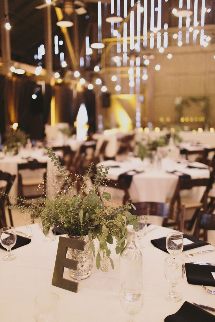 The room inside the barn was flipped after the ceremony, making space for the circular white dining tables decorated with lush centerpieces made of leaves and eucalyptus. Tables were each marked by a wooden letter so guests could find their seats.